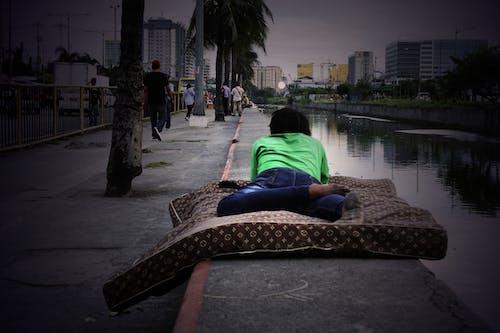 Бесплатное стоковое фото с бездомный, лежащий, манила, мужчина