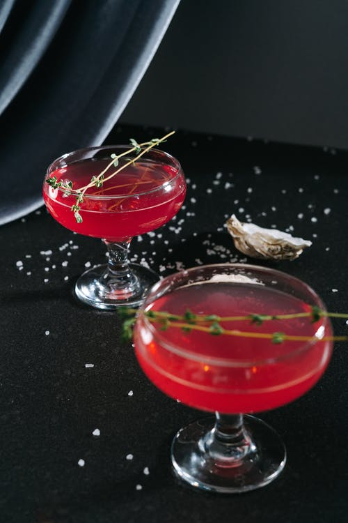 Two Red Beverages in Cocktail Glasses