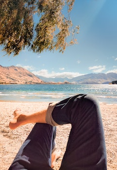 Person Wearing Blue Jeans Laying on Beach