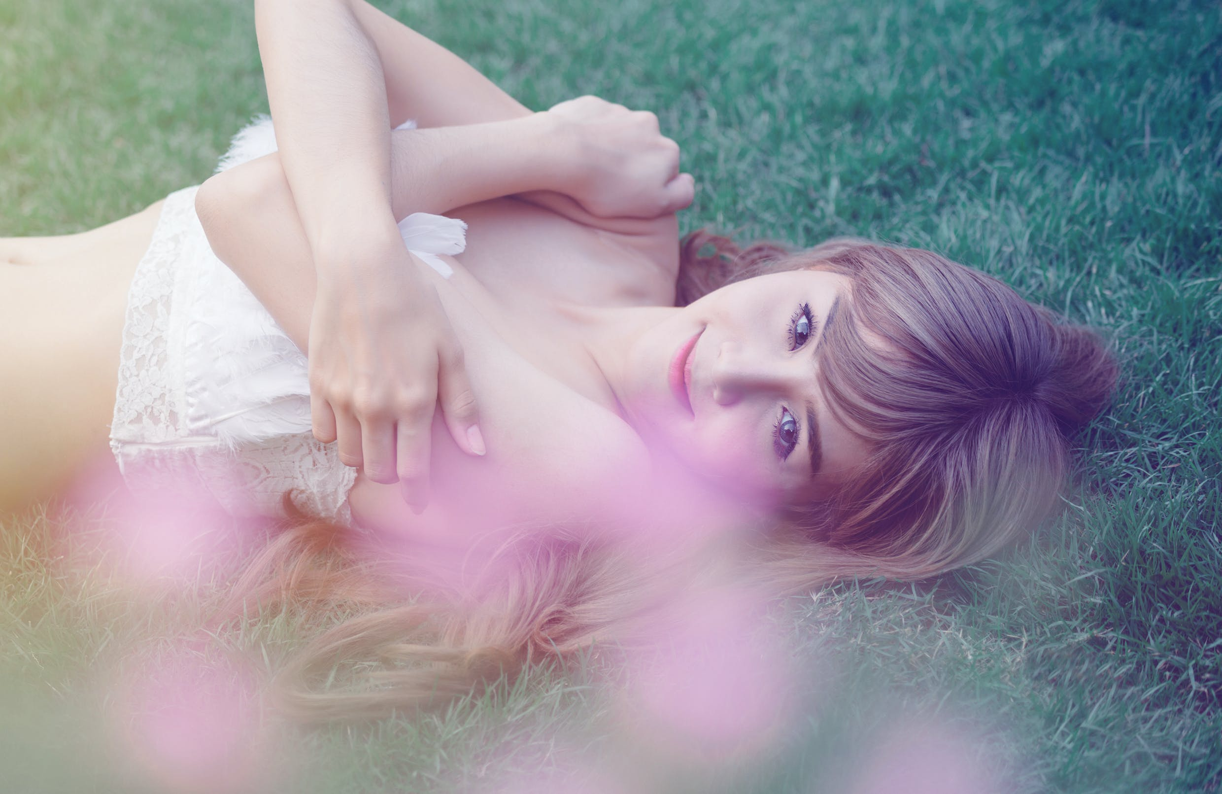 Photo of a Woman Lying on Green Wearing White Top