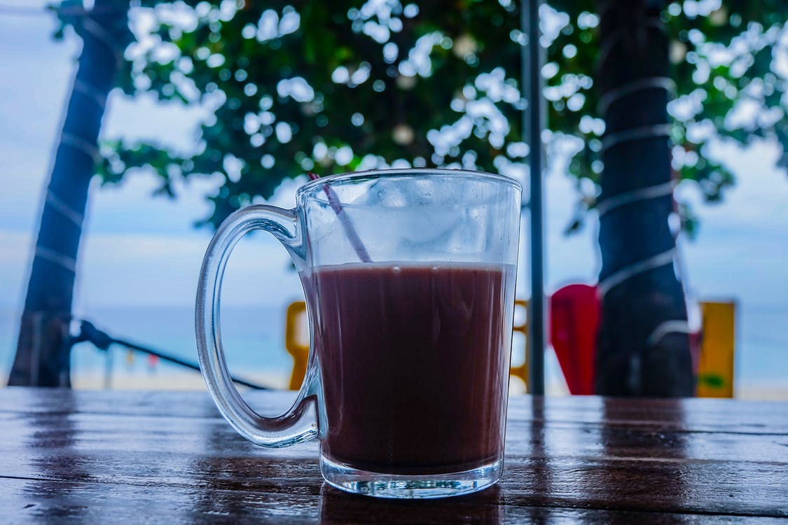 Clear Glass Mug With Beverage on Brown Wooden Table