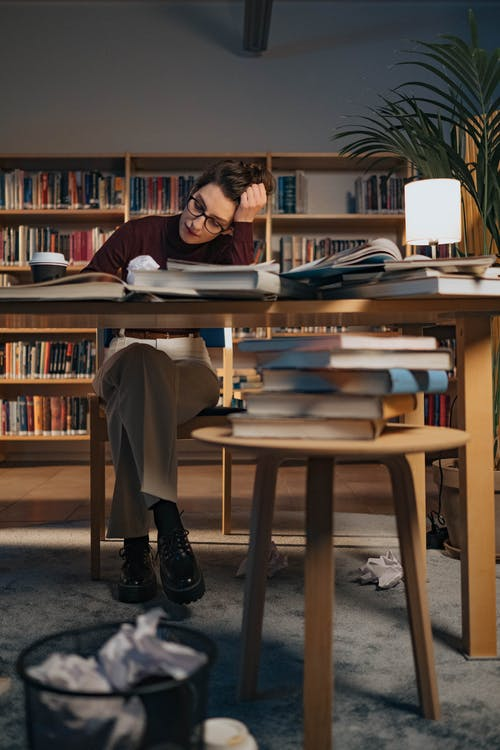 Woman Working of Her Work Desk with Books on Top