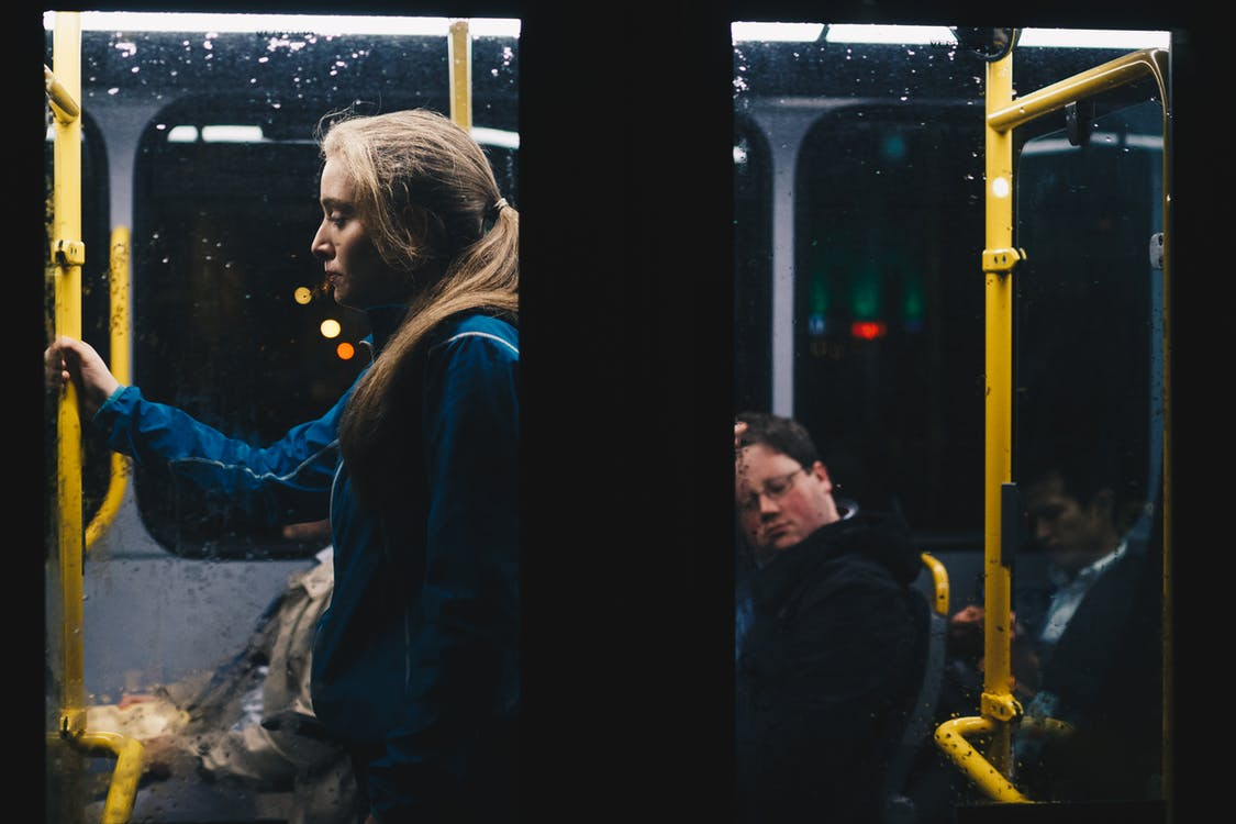 Photo of a Woman Standing Inside Bus