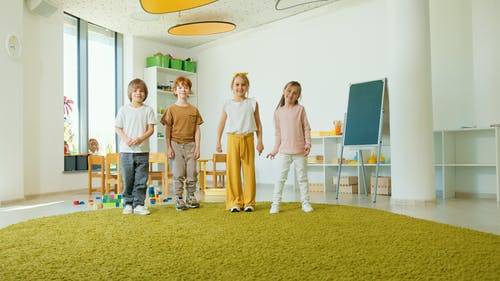 Smiling Children Standing Inside the Classroom