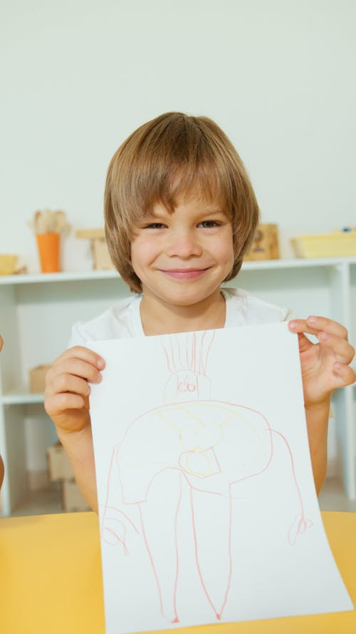 A Smiling Boy Showing His Artwork