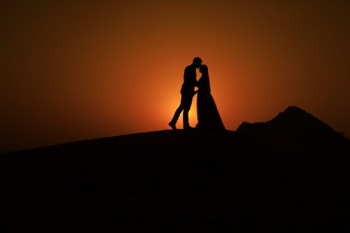 Silhouette of Couple Kissing during Golden Hour
