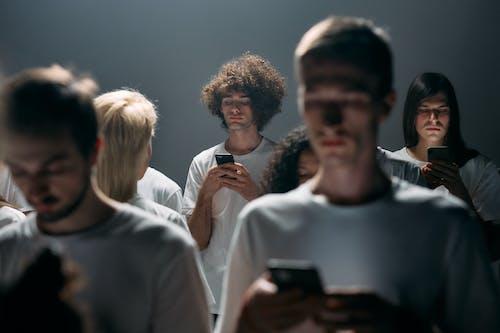Man in White Crew Neck Shirt Holding Black Smartphone