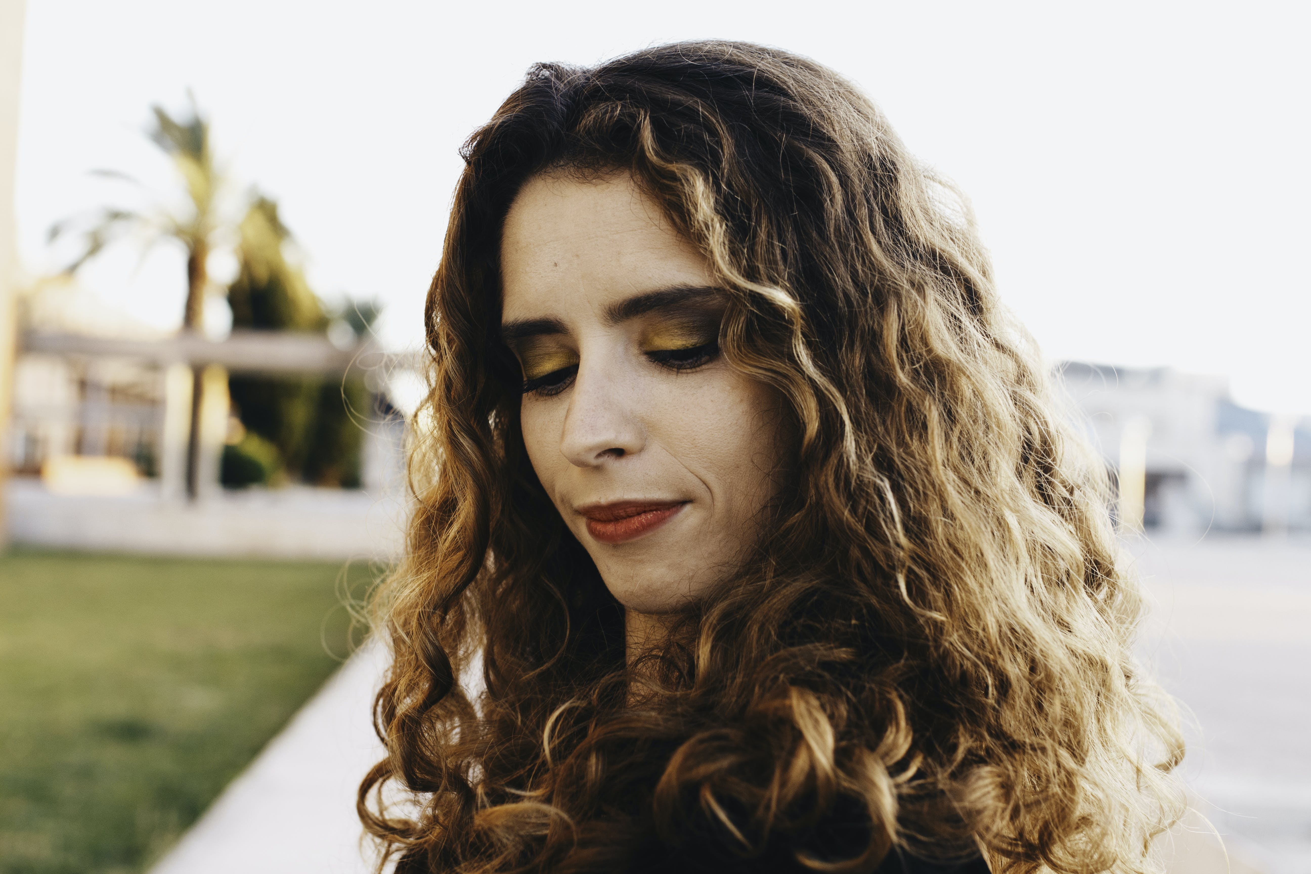 Curly Brown Haired Woman Wearing Black Shirt With Red Lipstick Looking Down