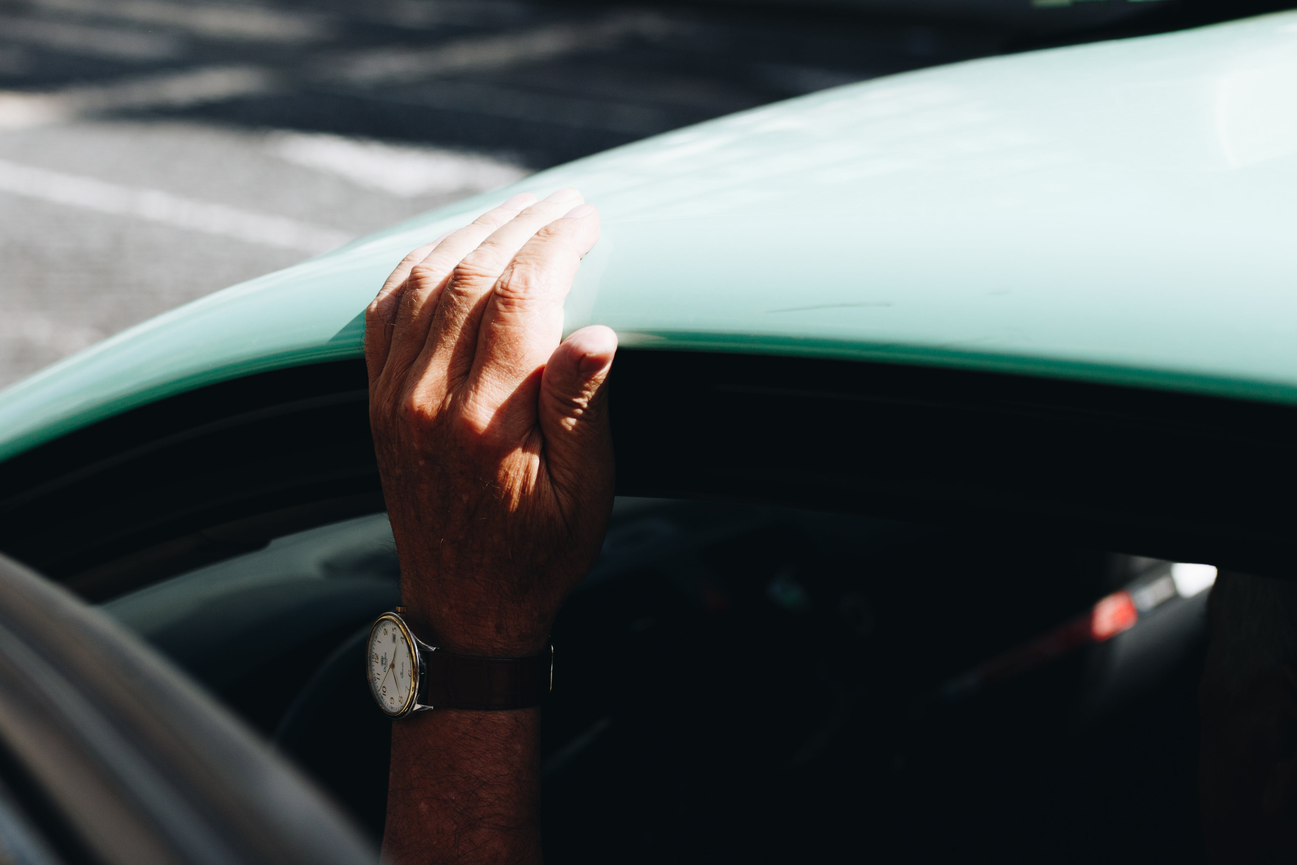 Person Wearing Round White Analog Watch Black Strap Holding on Vehicle Roof