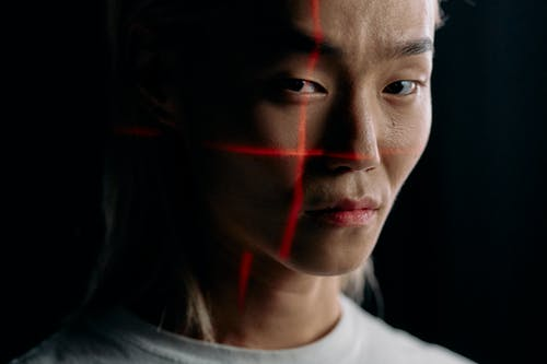 Close Up Photo of Man with Laser Lines on his Face