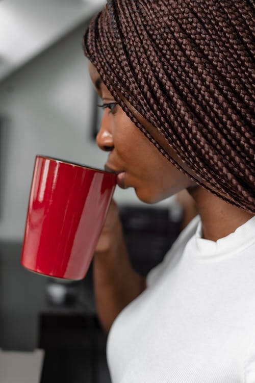 Woman with Braided Hair Drink from a Red Mug