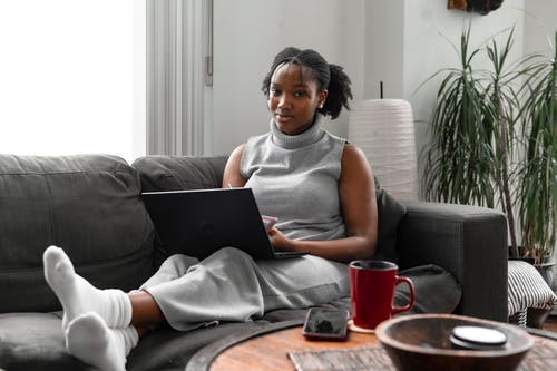 A Woman Using a Laptop While Sitting on a Couch