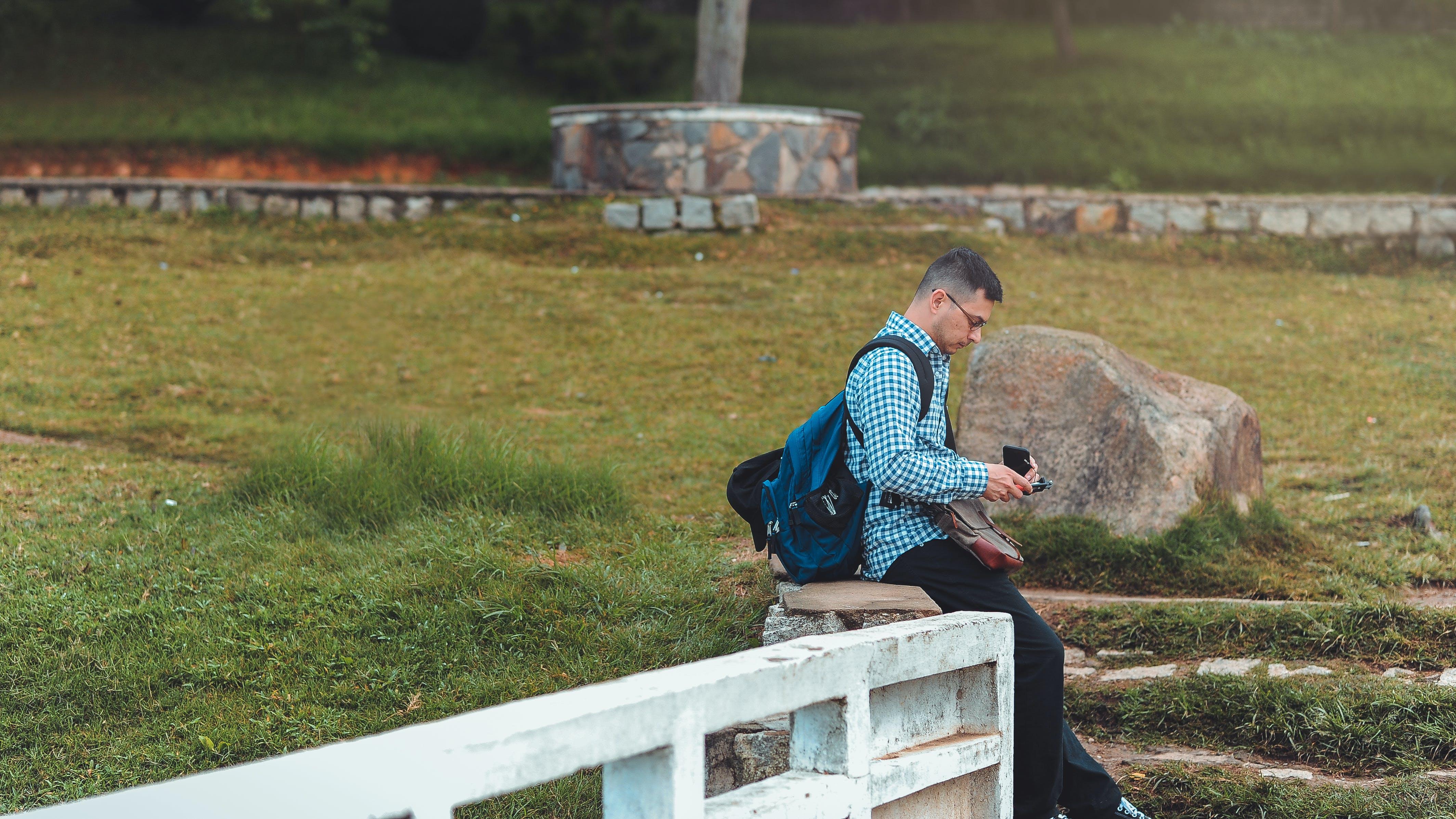 Man Sitting on White Railing Near Rock