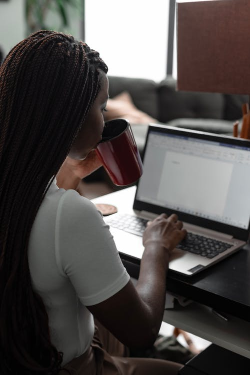 A Woman Drinking While Using a Laptop
