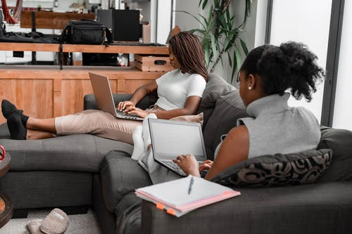 Women Using Laptops While SItting on a Couch