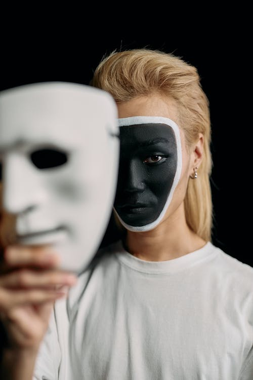 Selective Focus Photo of Man Holding White Face Mask