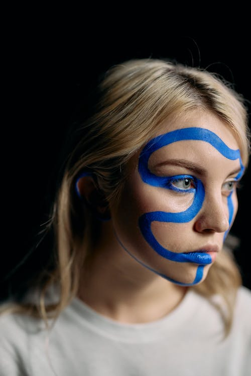 Close Up Photo of Woman with Blue Face Paint