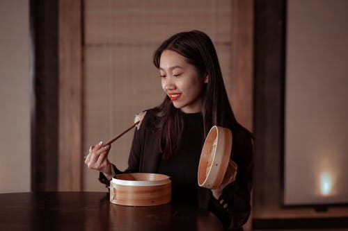 Woman in Black Jacket Holding Chopsticks with Dumplings