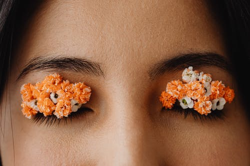 White and Orange Flower on Woman's Eyes
