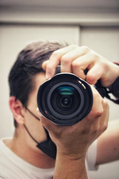 Man Holding Black Camera Lens