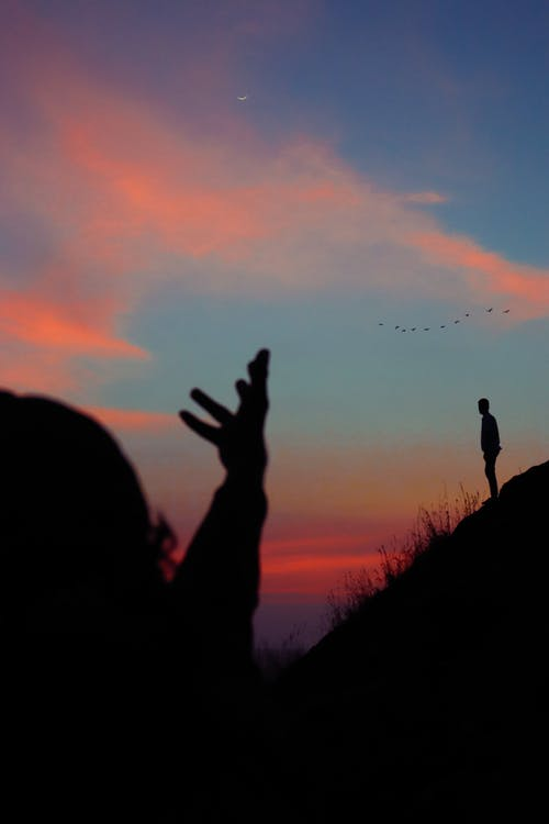 Anonymous travelers enjoying sunset during hiking trip