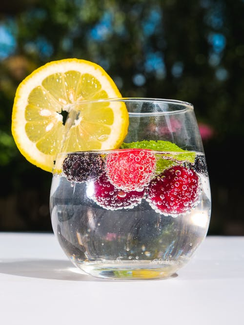 Clear Drinking Glass With Sliced Lemon and Strawberry