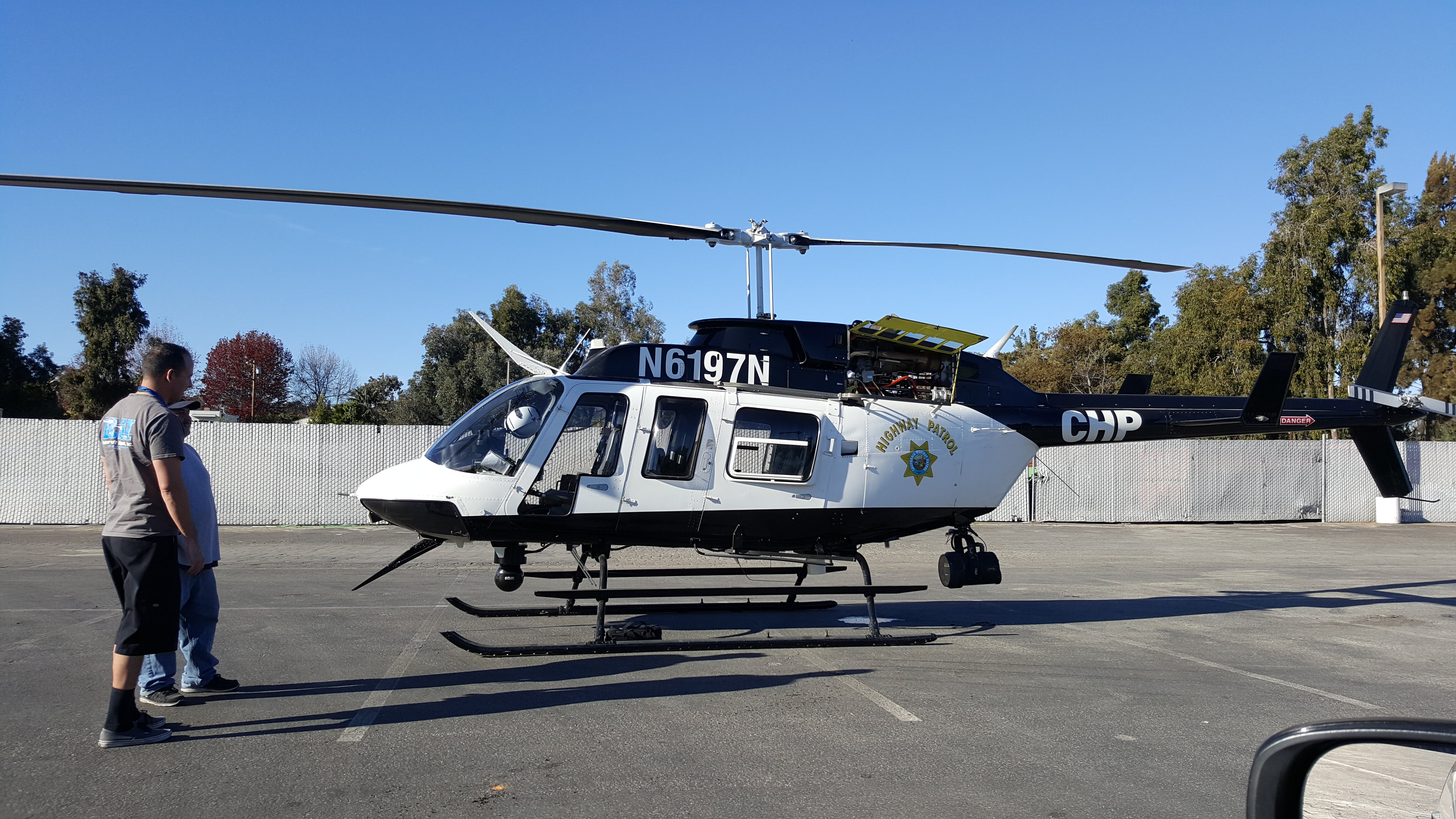 Photo of Two Person Standing in Front of White and Black Helicopter