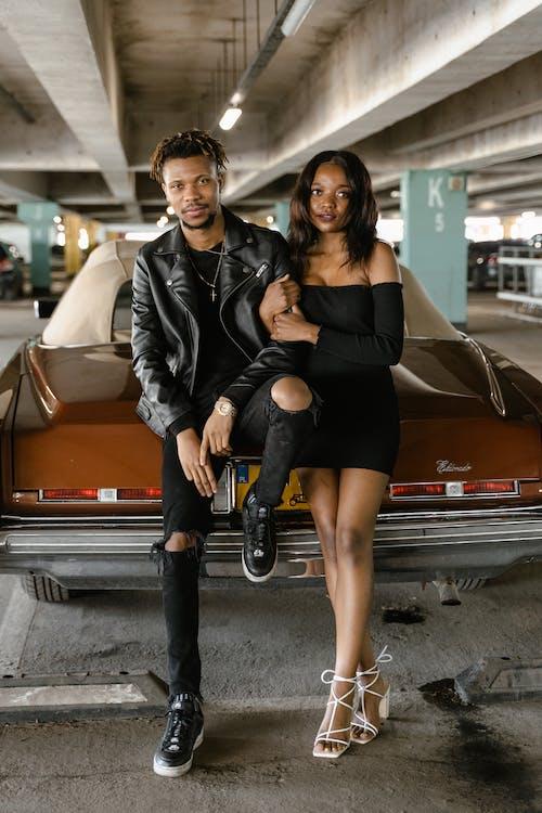 Stylish black couple near car