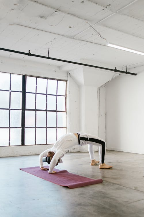 A Man Doing Yoga While Wearing a VR Headset
