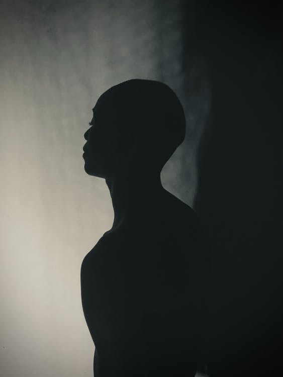 Silhouette of Man Standing Near Wall