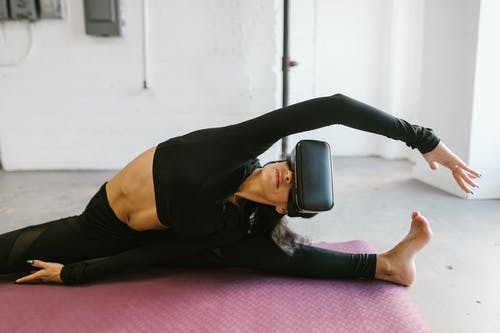 A Woman Doing Yoga While Wearing VR Goggles