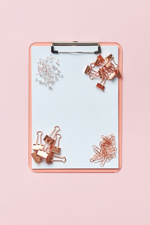 Some Paper Clips, Pins and Clip Binders on a Pink Clipboard