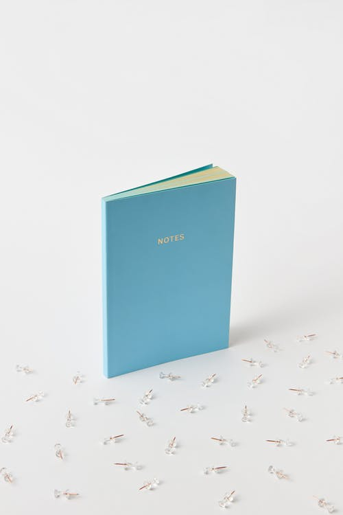 A Blue Notebook and Paper Pins