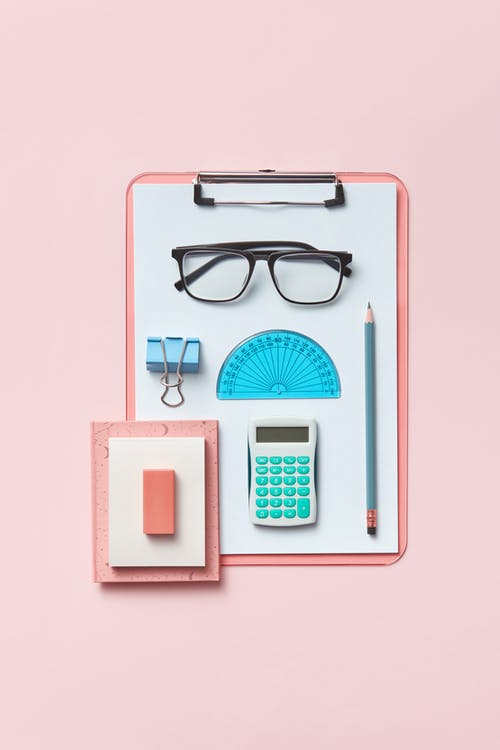 A Pencil, Calculator, Protractor, Clip Binder, and Glasses on a Pink Clipboard