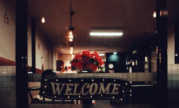 Black Welcome Signage Under Pendant Lamp Photography