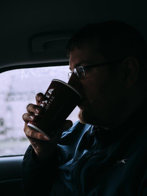Man in Blue Shirt Drinking on Black Ceramic Mug
