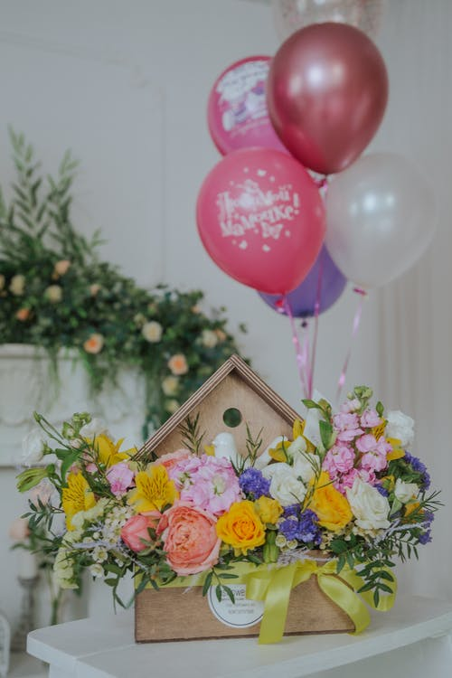 Pink and Yellow Flowers With White Wooden Box