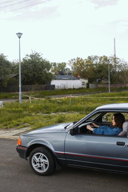 A Woman Driving a SIlver Car