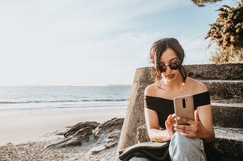 Foto profissional grátis de celular, litoral, mulher