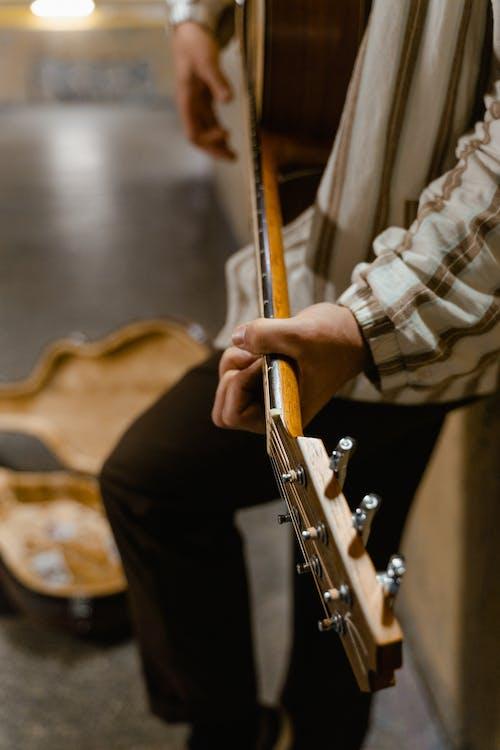 Man in Brown and White Stripe Dress Shirt Playing Guitar