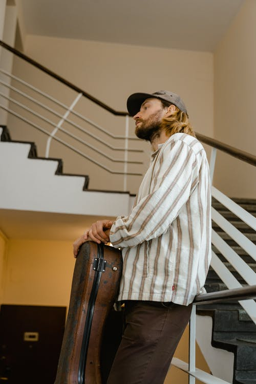 Man in White and Brown Stripe Dress Shirt and Black Pants Standing on Staircase