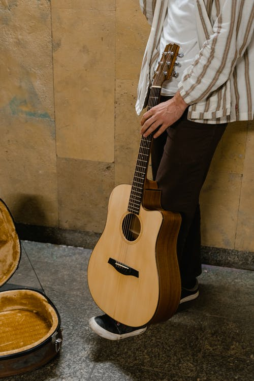 Man in White and Brown Stripe Button Up Shirt and Black Pants Holding Brown Acoustic Guitar