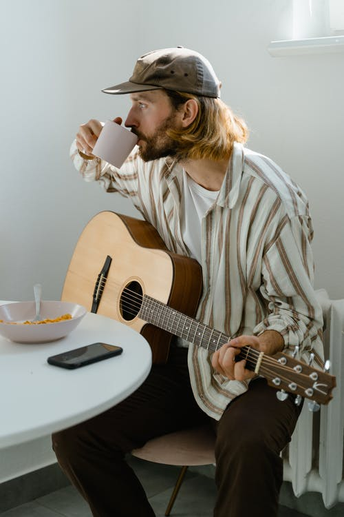 Man in White and Brown Stripe Dress Shirt Playing Acoustic Guitar