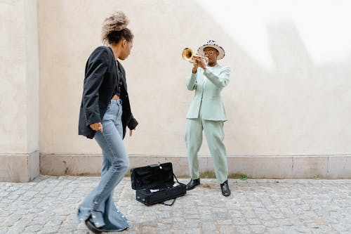 Woman Giving Coins to the Man Playing Trumpet