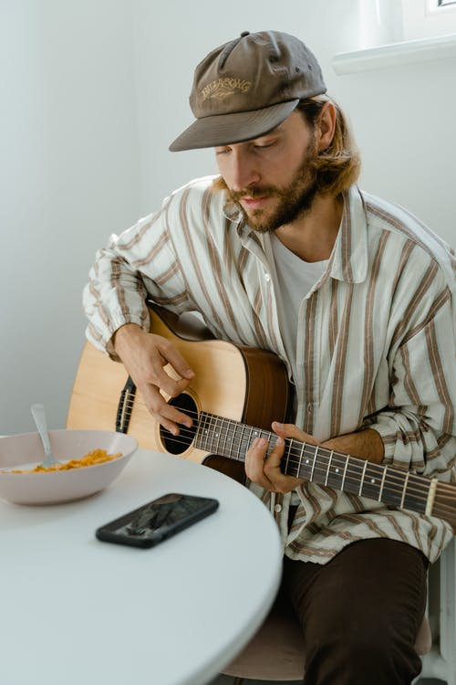 Man in White and Brown Stripe Button Up Shirt Playing Acoustic Guitar