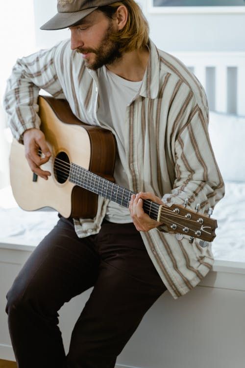 Man in White and Brown Stripes Dress Shirt Playing Acoustic Guitar