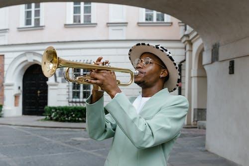 Man in White Robe Playing Trumpet