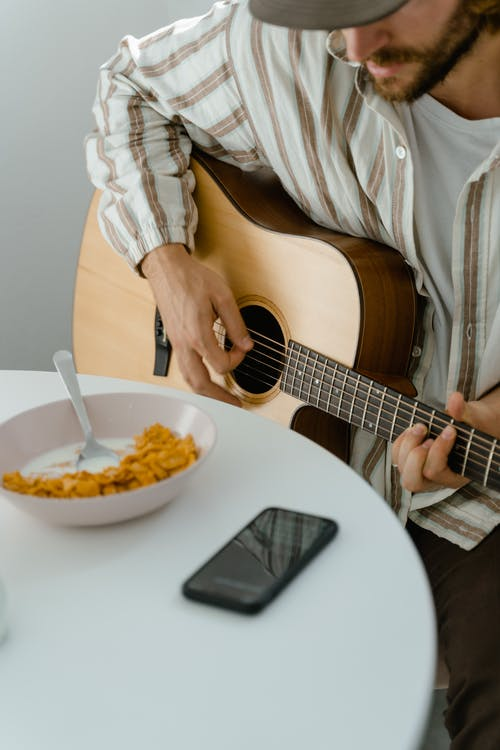 Man in White and Brown Stripes Button Up Shirt Playing Guitar
