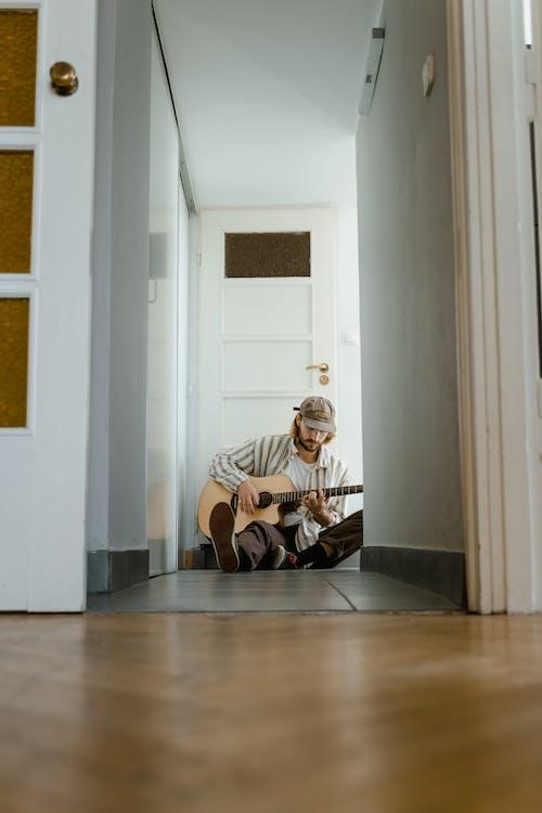 Man in White and Brown Stripe Shirt Playing Guitar