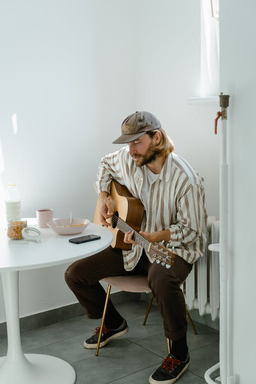 Man in White and Brown Stripe Button Up Shirt Playing Guitar